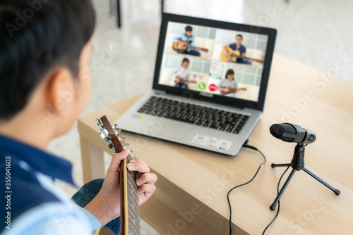Asian boy playing acoustic guitar virtual happy hour meeting for play music online together with friend in video conference with laptop for a online meeting in video call for social distancing Fototapet