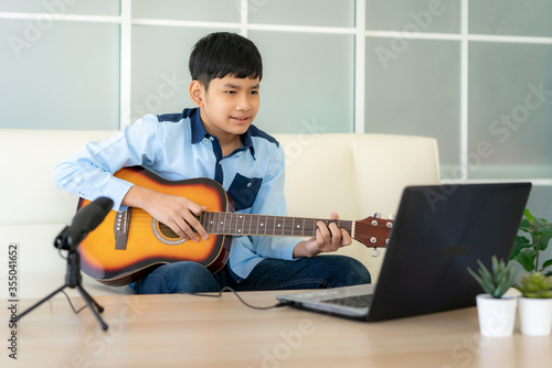 Fotografie, Obraz Asian boy playing acoustic guitar and watching online course on laptop while practicing at home