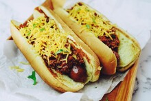 Homemade Chili Dogs Topped With Cheddar Cheese, Selective Focus