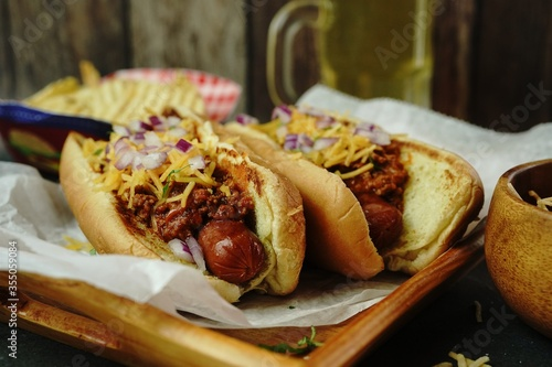 Photo Homemade Chili dogs topped with cheddar cheese, selective focus