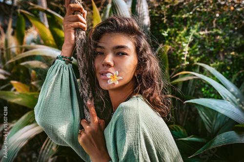 Fotografia beautiful young fashionable woman portrait at tropical background