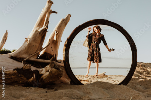 Fototapeta A  dark-haired woman smiles, walks along the beach and enjoys  in the reflection of the mirror the bright sun on a summer day
