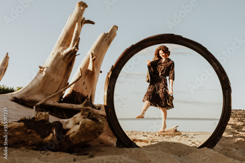 Fotografia, Obraz A  dark-haired woman smiles, walks along the beach and enjoys  in the reflection of the mirror the bright sun on a summer day