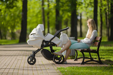 One Young Blonde Woman Sitting On Wooden Bench At Town Green Park In Warm, Sunny Summer Day. White Baby Stroller Beside Mother. Relaxing After Long Walk. Side View. Peaceful Atmosphere In Nature.