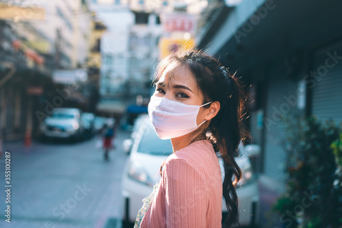 Foto Asian adult woman tan skin wear mask on face for new normal at outdoor