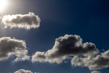 Beautiful Puffy Clouds In The Rays Of The Sun On A Blue Sky.