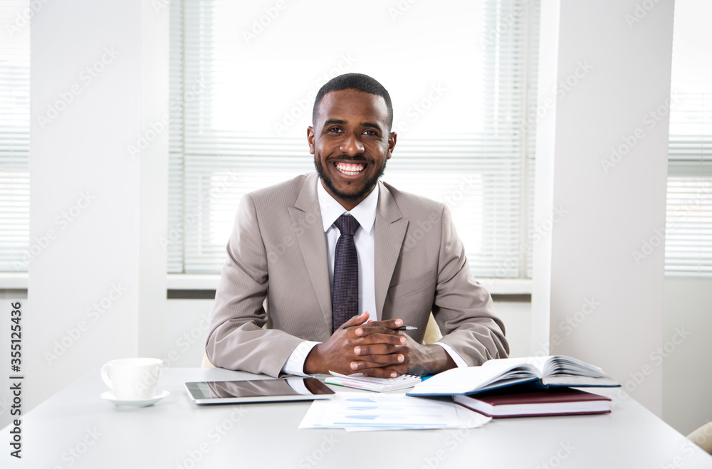 Fototapeta Happy handsome african american businessman smiling while looking at camera in office