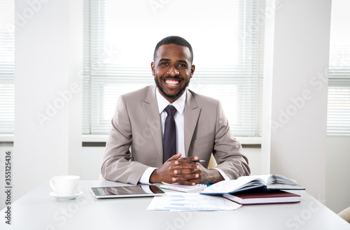 Fototapeta Happy handsome african american businessman smiling while looking at camera in office obraz