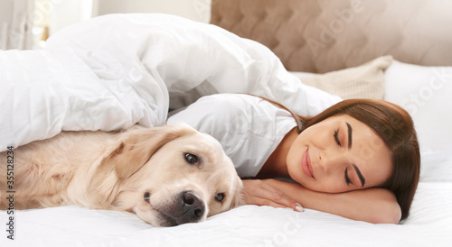 Cuadros en Lienzo Young woman and her Golden Retriever on bed at home, banner design