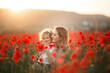 Beautiful smiling baby girl with mother are having fun in field of red poppy flowers over sunset lights, spring time