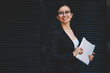 Leinwandbild Motiv Half length portrait of successful businesswoman dressed in elegant apparel holding modern tablet device in hands while smiling at camera standing near publicity area for your financial information