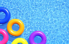 Top View Of Colorful Swim Rings On The Blue Water Background.