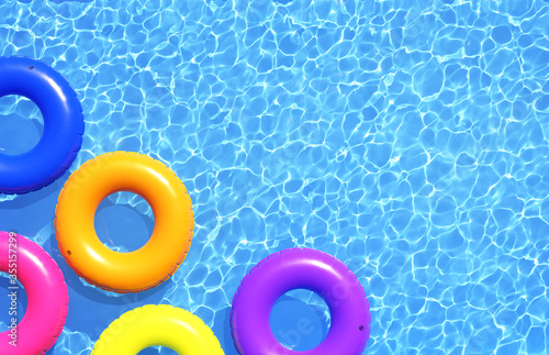 Obraz na plátně Top view of colorful swim rings on the blue water background.