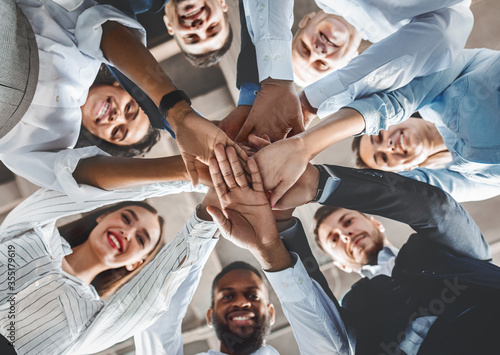 Fotomural Happy Coworkers Holding Hands During Teambuilding Meeting Standing In Office