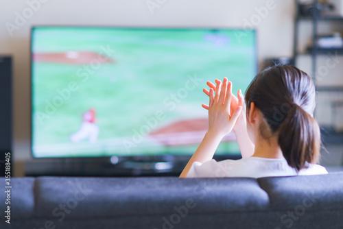 Photo 家でスポーツをテレビ観戦する若い女性のイメージ【プロ野球の動画配信サービス】