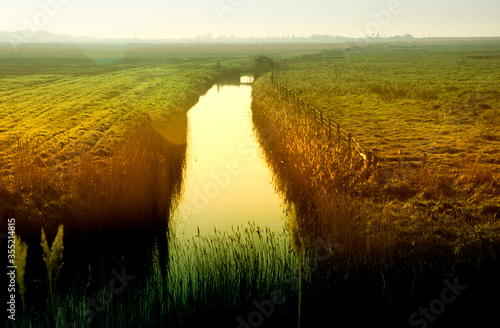 Obraz na plátne Evening sunset on fen marshland and water in land drain dyke