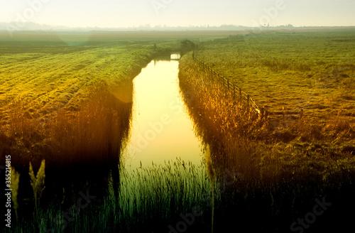 Fényképezés Evening sunset on fen marshland and water in land drain dyke