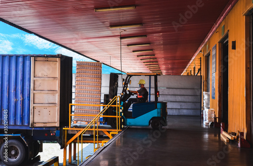 Photo Forklift stuffing-unstuffing pallets of cargo to container on warehouse leveler dock