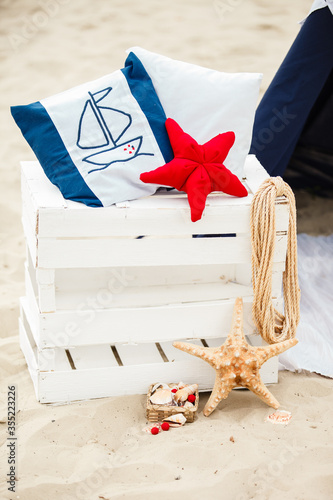 Decorative composition in marine style. Decorative cushion, sea stars, pillows and anchor. Beach holidays and vacation, relax Wall mural