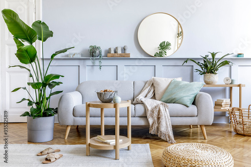 Photo Stylish living room interior with design grey sofa, coffe table, pouf, basket, shelf, mirror, tropical plants, decoration, carpet, pillows and elegant personal accessories in modern home decor