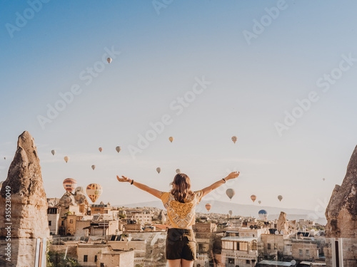 Photo Young woman with the background of Aerostatic balloons floating in the capadocci