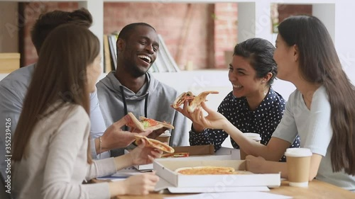 Fotografía Happy mutiethnic young students or business team people having fun share pizza t
