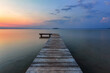 Old wooden jetty, pier reveals views of the beautiful lake, blue sky with cloud. Sunrise enlightens the horizon with orange warm colors. Summer landscape. Free space for text.