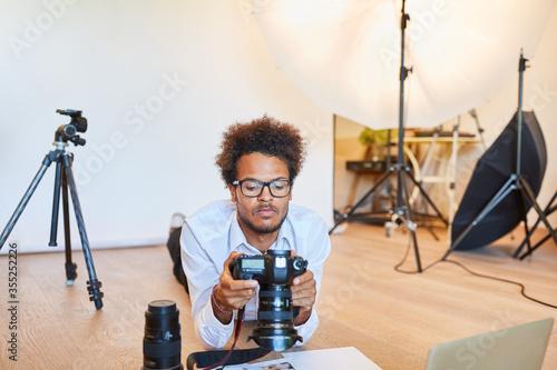 Photo Junger Fotograf kontrolliert digitale Kamera