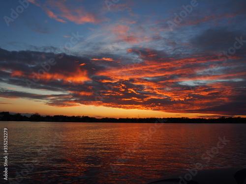 Michigan boaters enjoying a peaceful sunset on Lake Lansing in Haslett, Mi