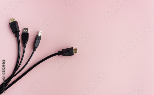 The black USB cable lies on a uniform background with room for text Wallpaper Mural