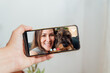 canvas print picture - hand holding a smartphone while having a video call with her friend and her dachshund dog