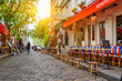canvas print picture - Cozy street with tables of cafe in quarter Montmartre in Paris, France