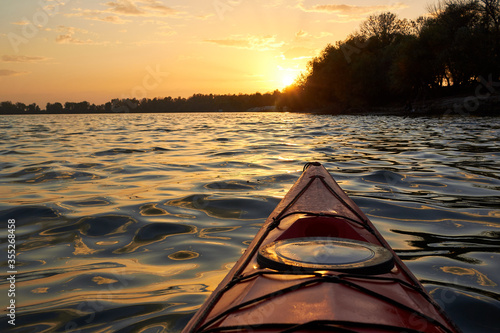 Fototapeta View on sunset over river from the bow of red kayak. Kayaking, canoeing, paddling. Meeting sunset on kayak. obraz