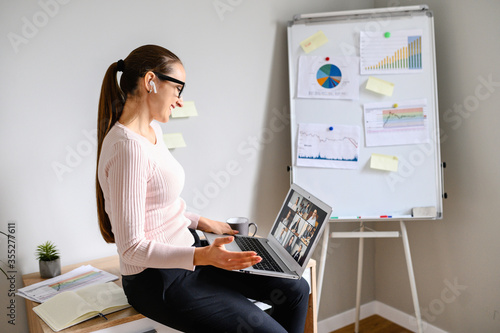 Obraz Remote works. Positive young woman is using laptop for business meeting with partners - fototapety do salonu