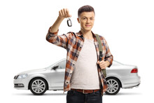 Male Teenager Holding A Car Key From His New Silver Car