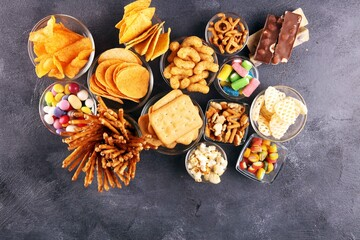 Salty snacks. Pretzels, chips, crackers in glass bowls on table