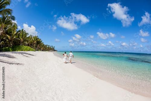 Stampa su Tela Newlyweds holding hands hugging at white sandy tropical caribbean beach landscap