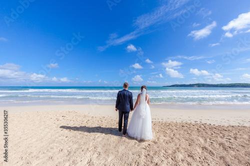 Fotografia Newlyweds holding hands hugging at white sandy tropical caribbean beach landscap