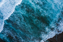 Aerial View Directly Taken Above Of Some Tidal Waves Coming From The Ocean And Splashing Along The Coastline In Indonesia.