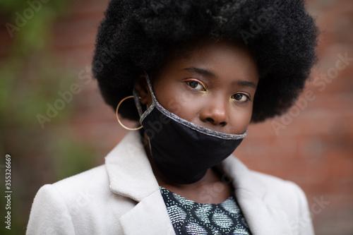 Obraz Young dark-skinned girl wearing protective fabric face mask below her nose in coronavirus pandemic, COVID-19. - fototapety do salonu