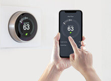 A Person Using A Smart Phone Application Saving Energy With A Wireless Smart Thermostat On A White Background.