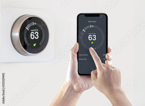 Obraz na płótnie A person using a smart phone application saving energy with a wireless smart thermostat on a white background