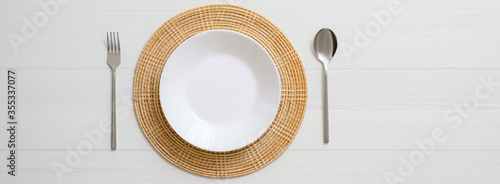 Fototapeta White plank dinning table with white ceramic plate on placemat and silverware obraz