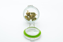 Marijuana From A Dispensary In A Glass Container On A White Surface.  Several Dense Marijuana Buds, Glass Container Has A Green Seal.