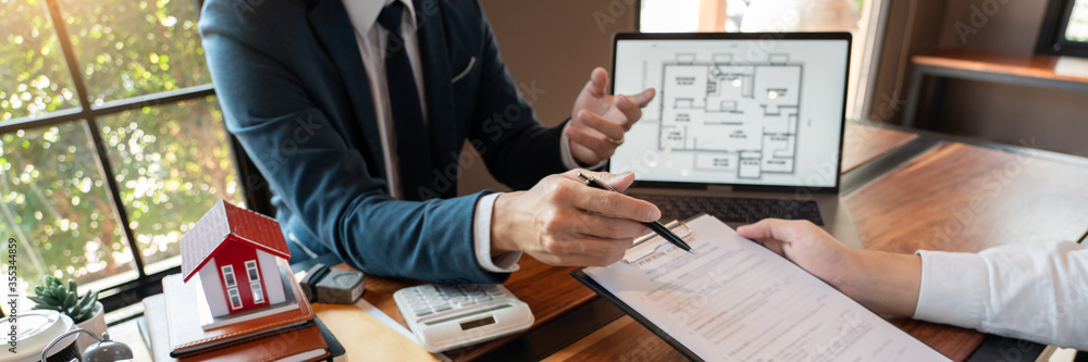 Fototapeta Real Estate broker or sale agent giving consultation to customer about buying house sign agreement document contract. Home loan concept.