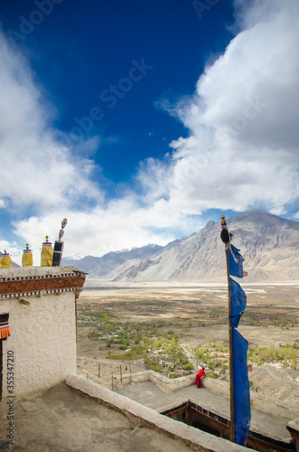 Fotografie, Obraz monk in red looks out into the distant mountains in ladakh