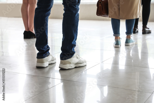Fototapeta Group of people standing with social distance indoors. Concept of epidemic obraz