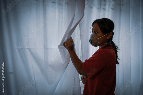 Cuadros en Lienzo A woman with face mask on anxiously peeks through her window curtains anticipating dangers coming her way