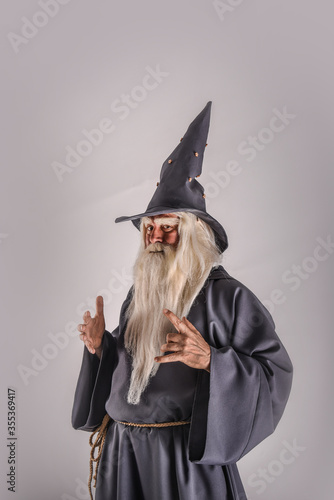 Fotografie, Tablou A stern grey-haired bearded wizard in a gray cassock and a cap is practicing sorcery and doing magic against a light background