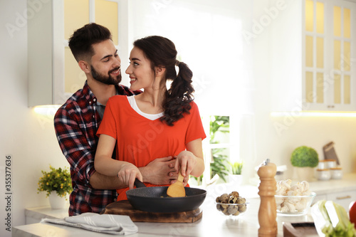 Fototapeta Lovely young couple cooking together in kitchen obraz